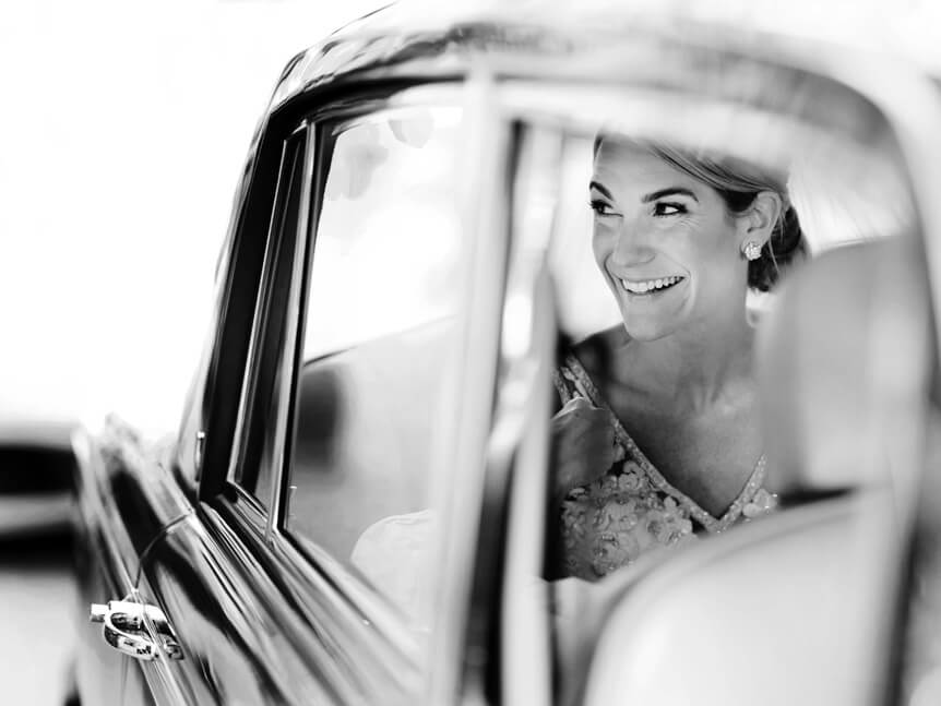 Professional photographer, Alison Conklin, on why the FUJIFILM GFX system is so good for location portrait photography. Black and white image through the window of a classic car of a smiling bride who is sitting in the back seat.