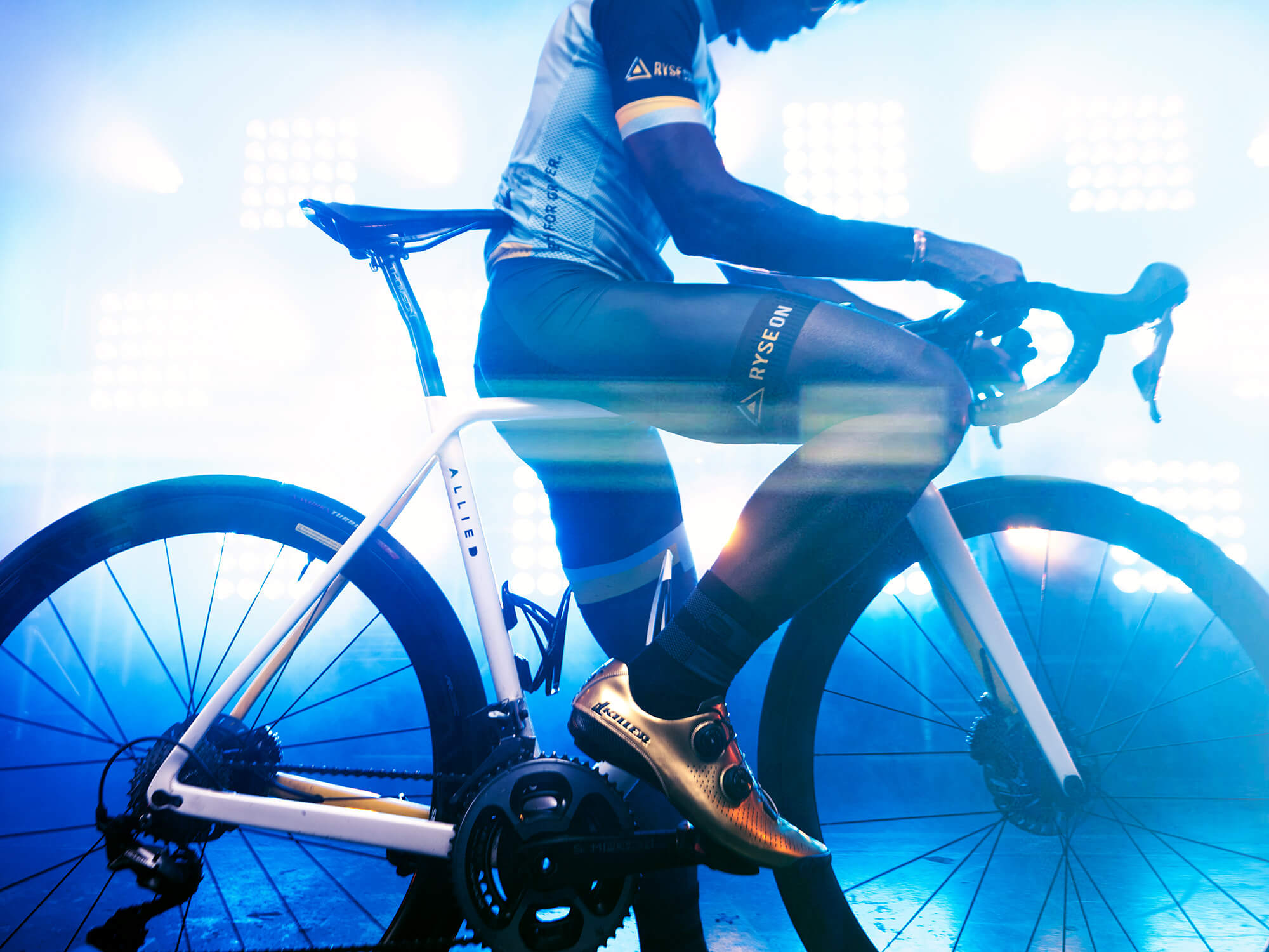 Cyclist in gold shoes sat on bike in front of bright, blue lights