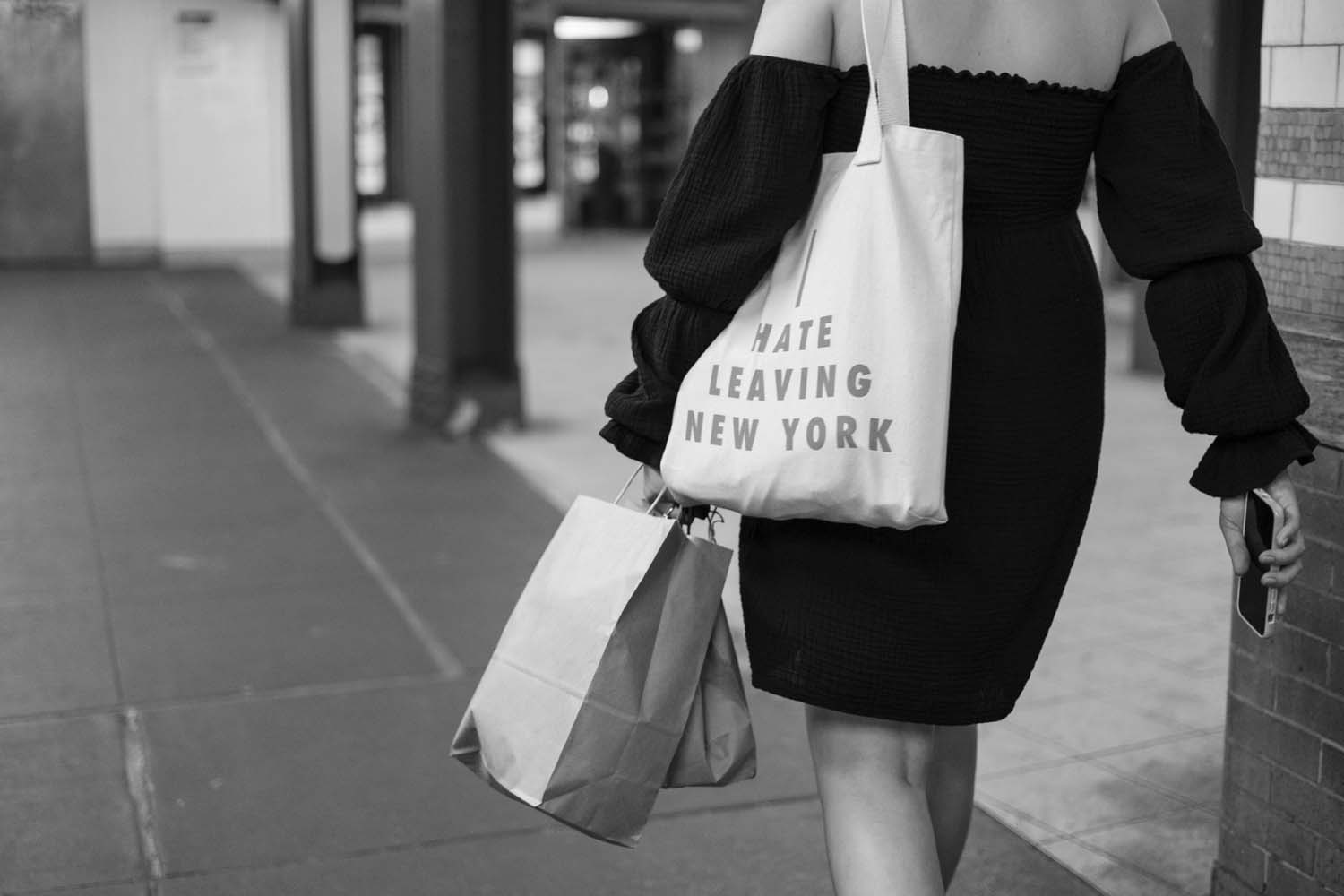 Woman in black dress carrying a tote bag reading I hate leaving New York