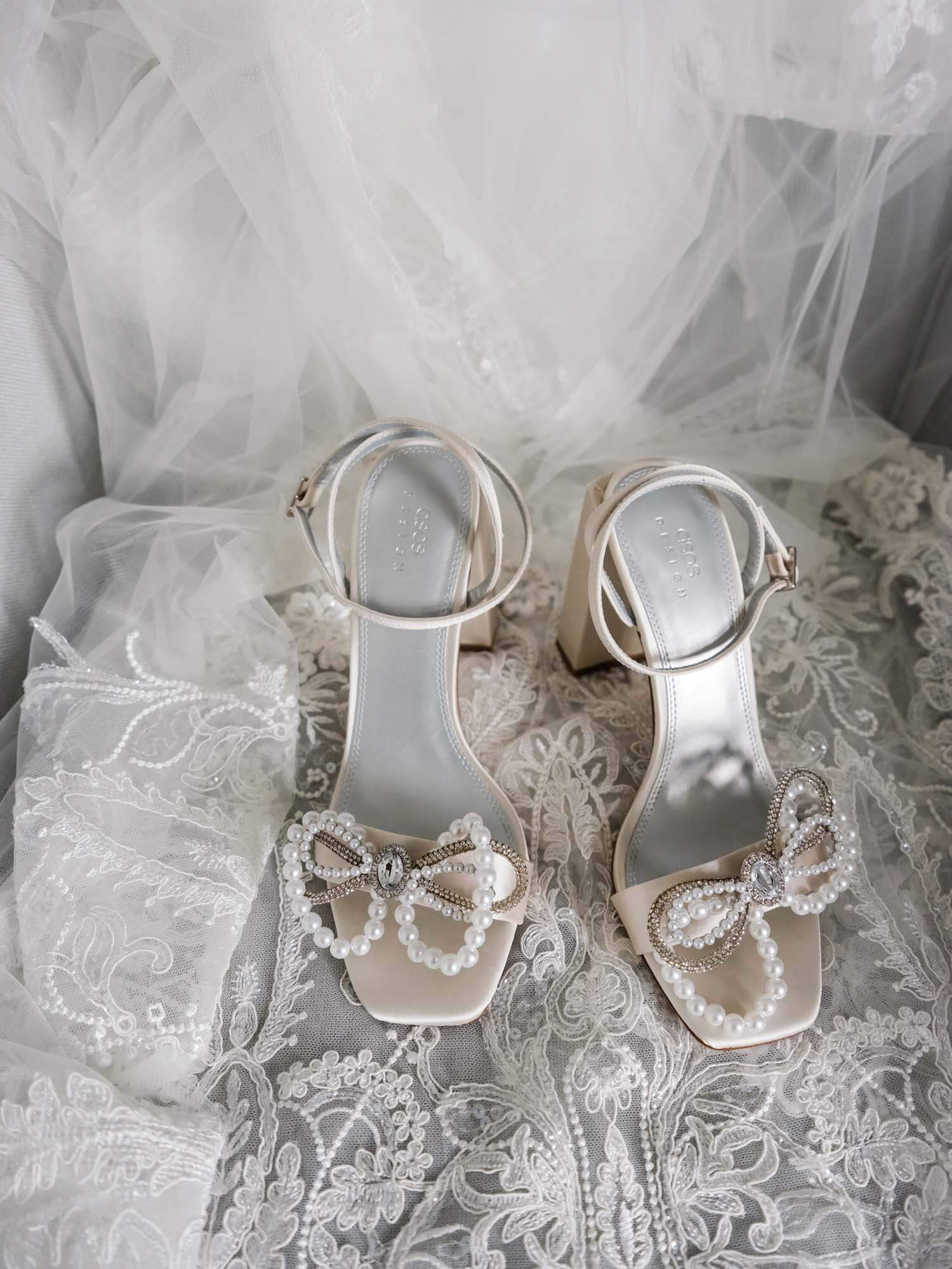 Bride's white shoes on veil-covered chair